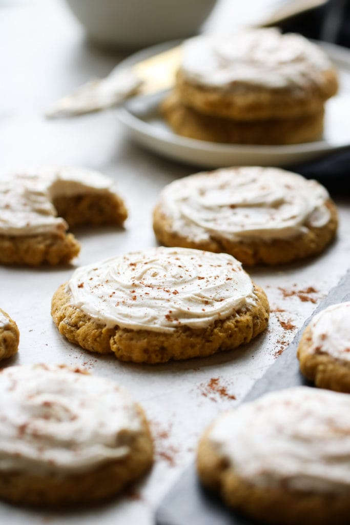 Several pumpkin cookies on a counter topped with cream cheese frosting and sprinkled with cinnamon