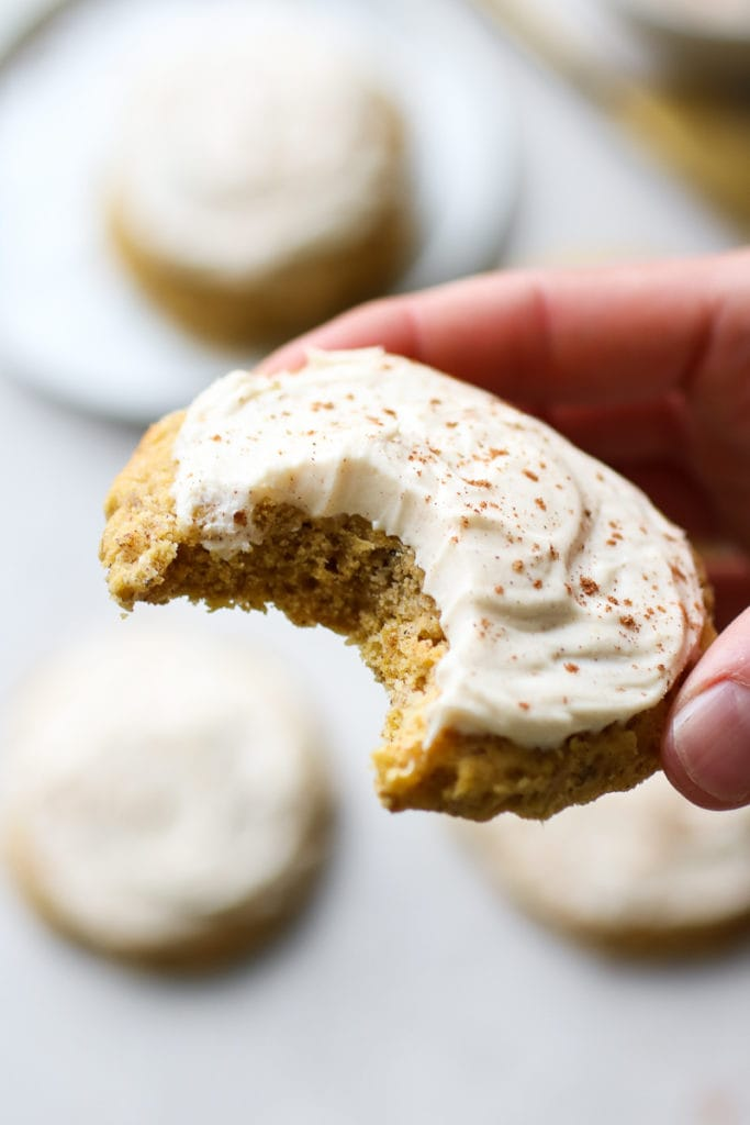 A Soft Pumpkin Cookie with a thick layer of cream cheese frosting and a bite out of it.