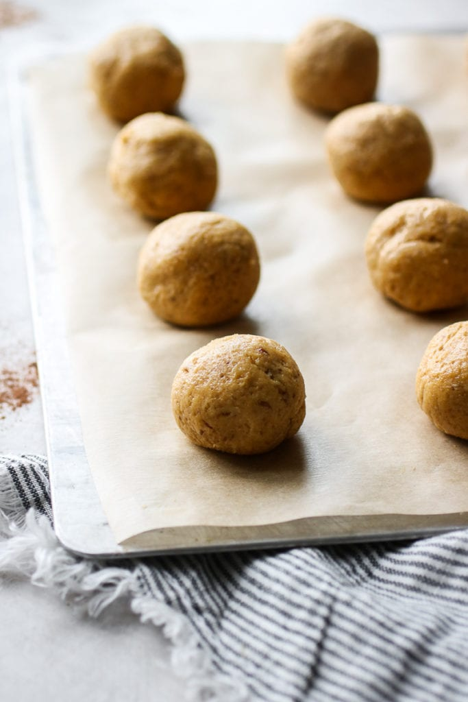 Balled pumpkin cookie dough lined up on a baking sheet on parchment paper