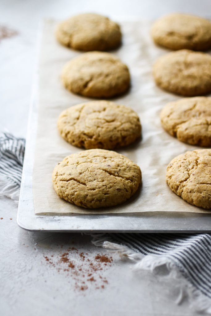 Pumpkin cookies fresh from the oven lined on a parchment-covered baking sheet