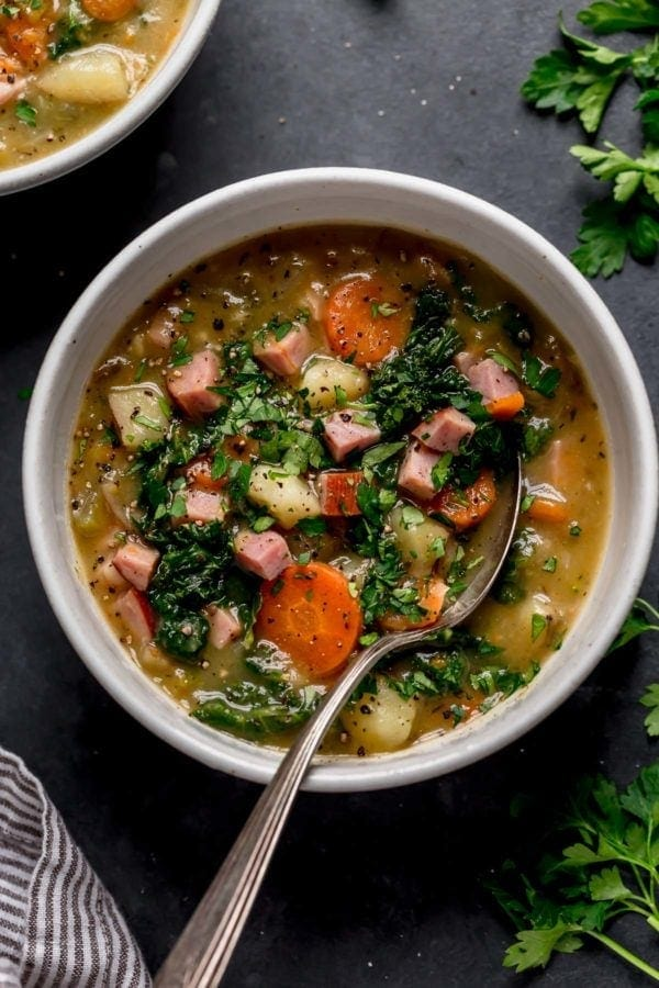 A speckled bowl filled with creamy ham and potato soup topped with kale and herbs