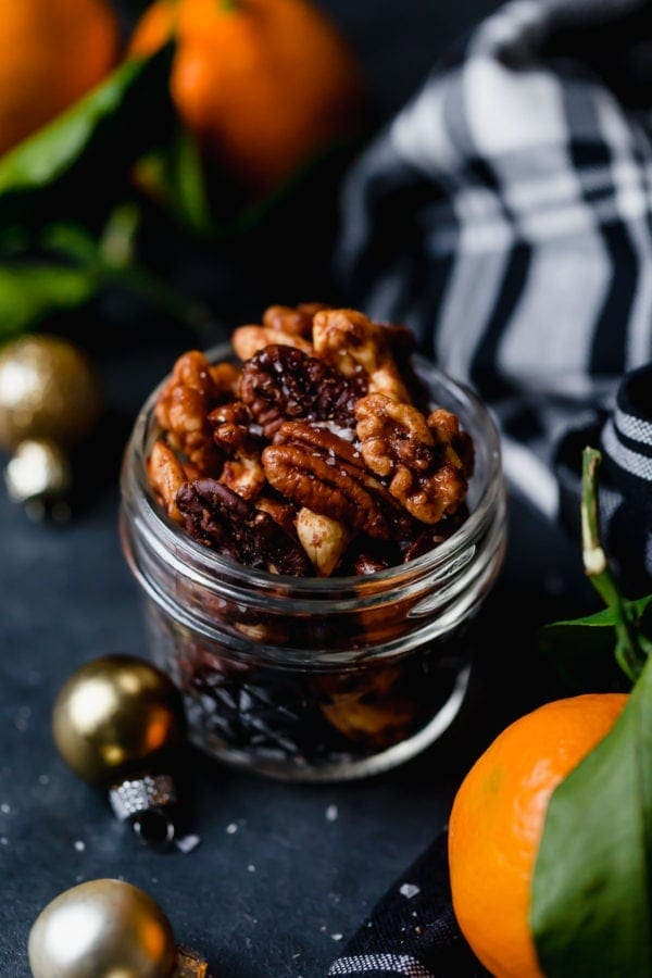 A small jar of Slow Cooker Spiced Nuts (includes cashews, almonds, and pecans) on a dark surface with tangerines, a black and white plaid napkin, and small gold ornaments surrounding the jar.