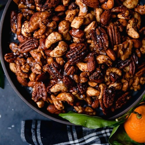 Overhead view of a black bowl on a dark grey surface filled with Slow Cooker Spiced Nuts (includes cashews, almonds, and pecans).