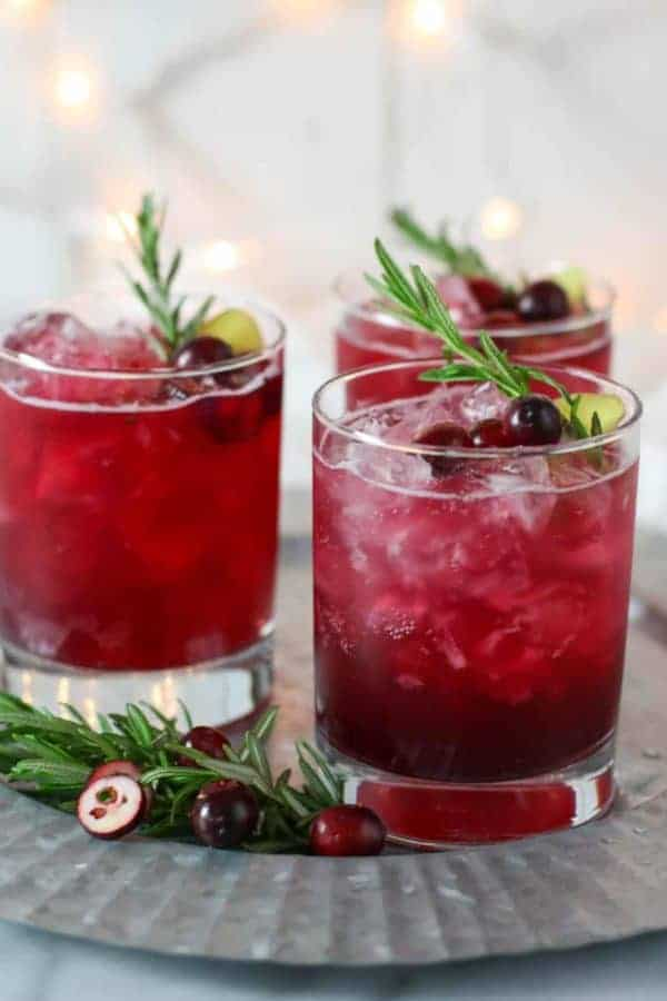 Three glasses of sparkling cranberry kombucha mocktail in clear glasses garnished with fresh cranberries and rosemary sprigs.