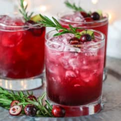 Sparkling Cranberry Kombucha Mocktail in three old-fashioned glasses and garnished with cranberries, ginger, and a rosemary sprig.