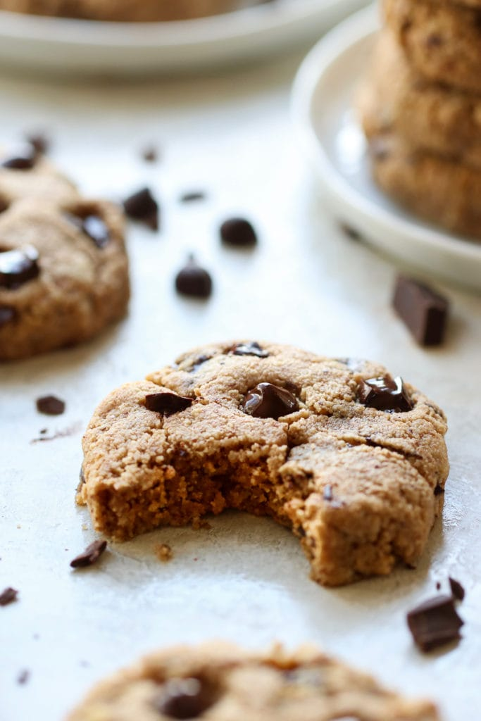 Paleo Chocolate Chip Cookies on a white platter. One of the cookies has a perfect bite out of it. Chocolate chunks and chips scattered about.
