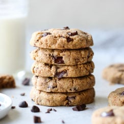 Five chocolate chip cookies stacked on top of each other with a glass of milk in the background.