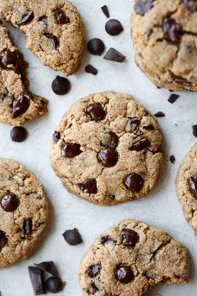 Several Paleo Chocolate Chip Cookies on a white platter with chocolate chunks and chips scattered about.