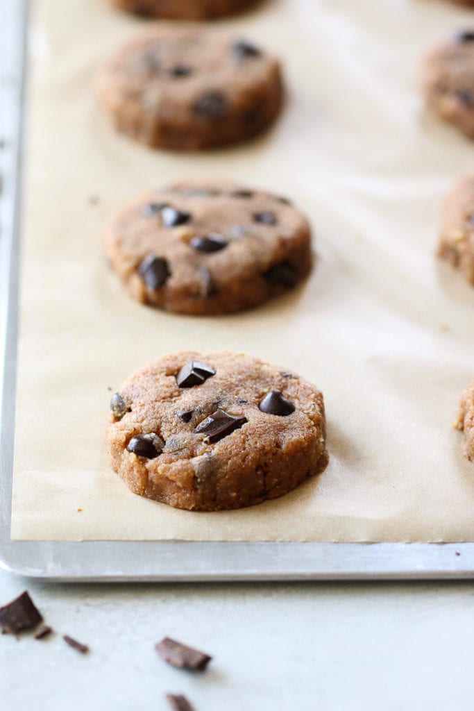 Paleo Chocolate Chip Cookies on a cookie sheet lined with parchment paper ready for the oven.