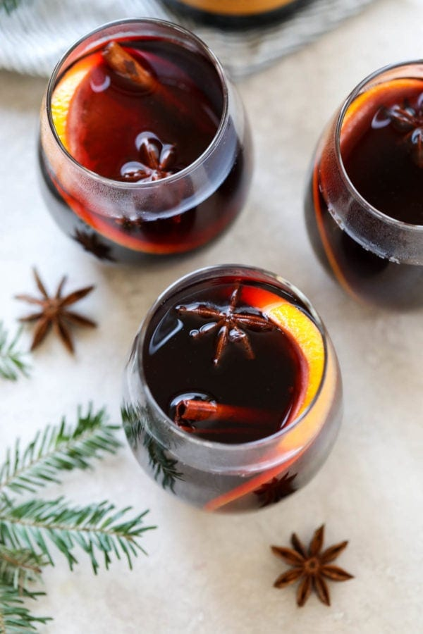 overhead shot of mulled wine in glasses with orange slices and cinnamon sticks