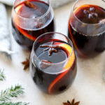 Three glasses filled with slow cooker mulled wine and garnished with orange slices and anise stars.