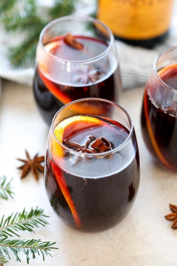 Festive shot of a mulled wine recipe poured into glasses with orange slices and cinnamon sticks.