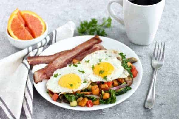 Fried eggs over sauteed veggies with a side of bacon on a white plate