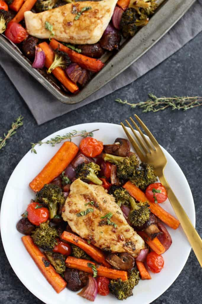 One-Pan Balsamic Chicken Veggie Bake on a white plate with a gold fork laying next to it