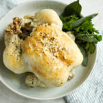 A roasted chicken in a cream speckled bowl with fresh herbs on the side.
