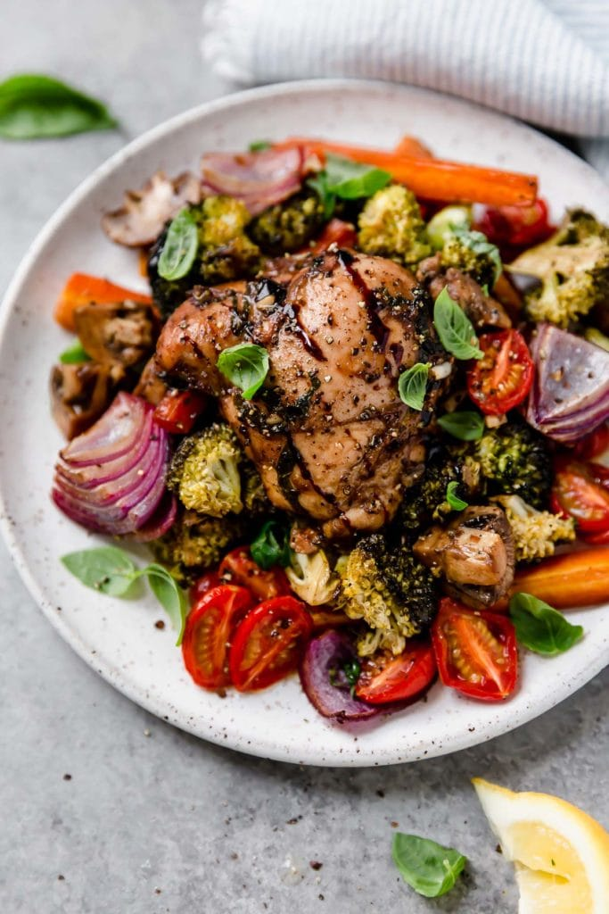 A colorful image of One-Pan Balsamic Chicken Veggie Bake plated on white plate.
