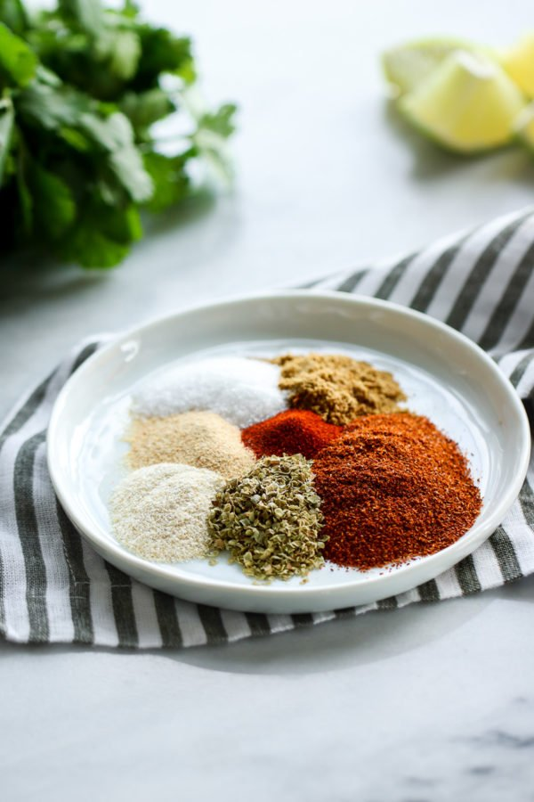 All the spices for homemade taco seasoning in a shallow white dish