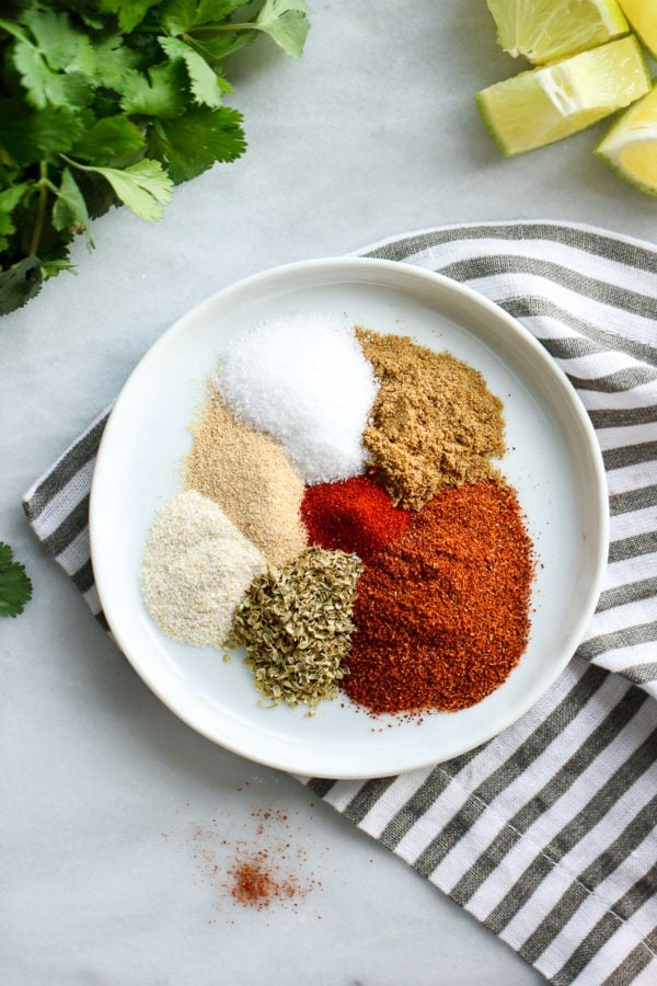 All seasoning for homemade taco seasoning on a shallow white bowl onto a grey and white striped dish cloth