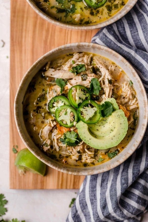 Two bowls of Slow Cooker White Chicken Chili on a cutting board draped with a grey and white napkin.