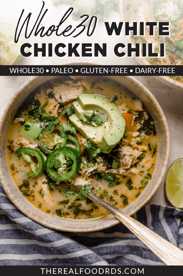An overhead view of Slow Cooker White Chicken Chili in a stoneware bowl topped with avocado slices and diced jalapeno.