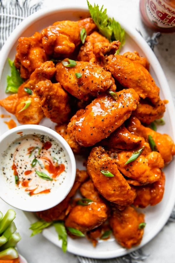 Overhead view of a platter of crispy baked buffalo wings on a white platter