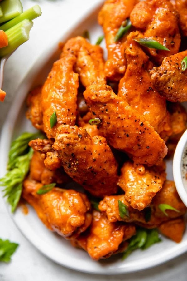 Crispy Buffalo wings covered in spicy buffalo sauce topped with crack pepper and scallions served on a white platter