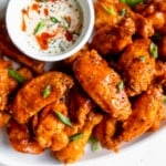 Crispy Baked Buffalo Wings piled high on a white serving platter with a bowl of ranch for dipping