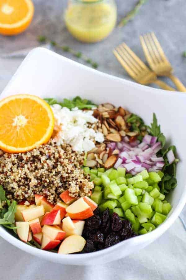 Arugula Salad with Apples, Almonds, Quinoa and Goat Cheese ingredients in a white bowl