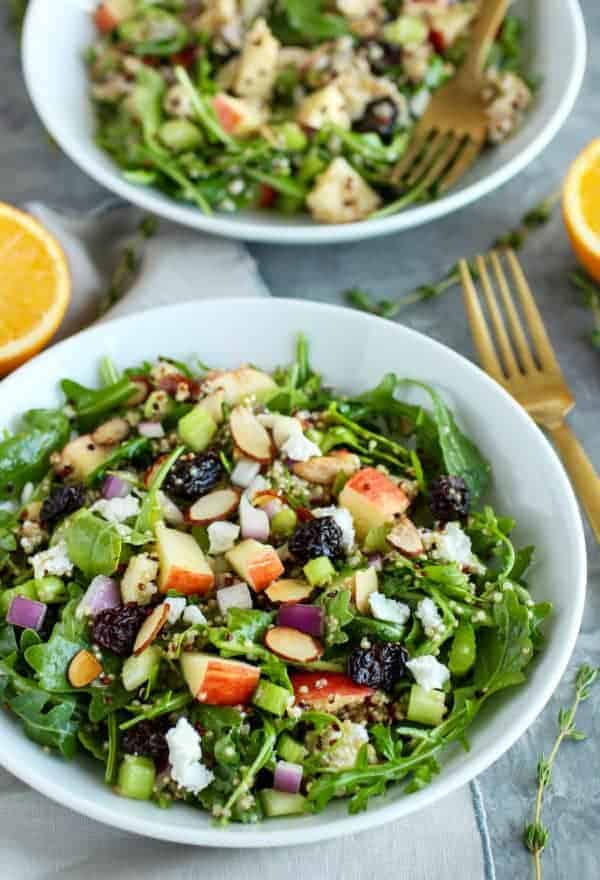 Arugula Salad with Apples, Almonds, Quinoa and Goat Cheese in a white bowl