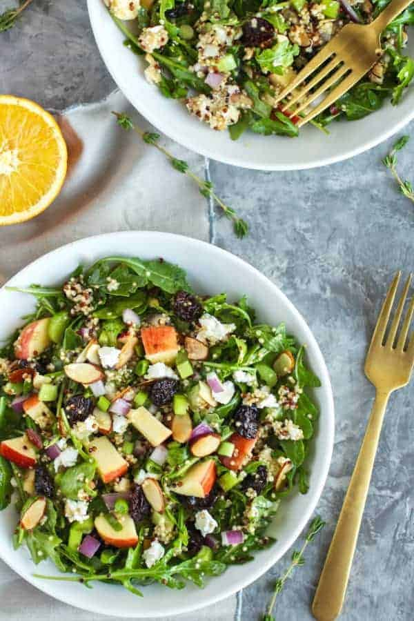 Arugula Salad with Apples, Almonds, Quinoa and Goat Cheese in a white bowl with a gold spoon