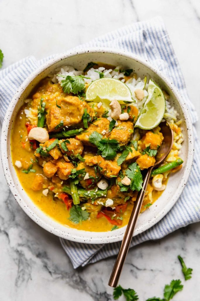 An overhead view of chicken curry with sweet potatoes topped with cilantro, cashews, and lime wedges in a speckled bowl