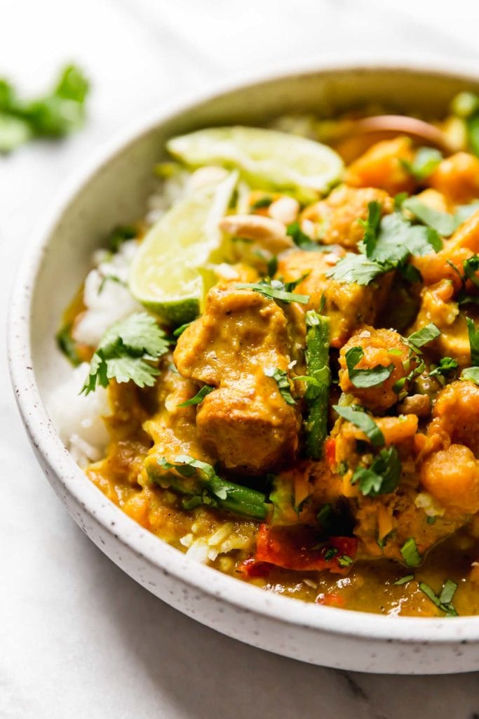 Creamy Chicken Curry with sweet potatoes topped with cilantro and lime wedges in a speckled bowl