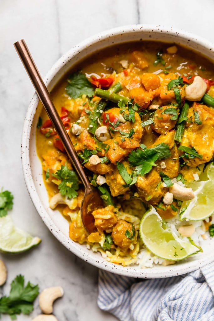 Instant Pot Chicken Sweet Potato Curry served over white rice in a white speckled bowl garnished with cilantro, lime wedges and cashews.