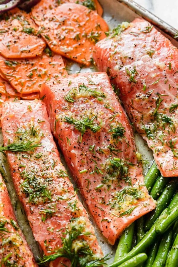 Salmon fillets on a baking sheet topped with marinade and fresh dill, ready for the oven.