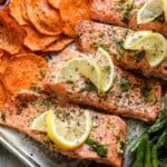 A close view of salmon and sweet potato rounds on a sheet pan