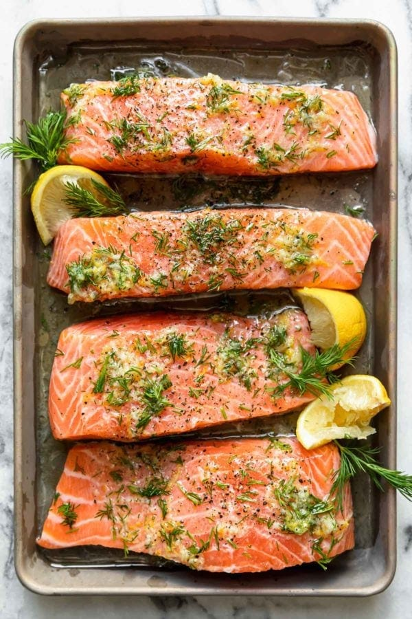 Four salmon fillets topped with marinade, fresh dill, and lemon wedges in a baking dish.