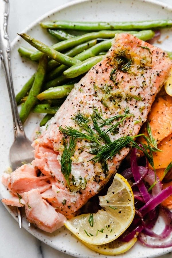 A salmon fillet plated with green beans, purple onion, and sweet potato rounds with a forkful of flakey salmon on the side.