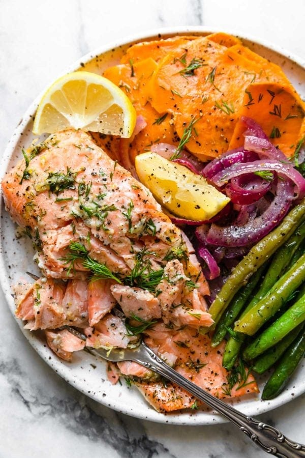 A salmon fillet, green beans, sweet potato slices, and red onion slices, plated on a speckled plate and topped with lemon wedges.