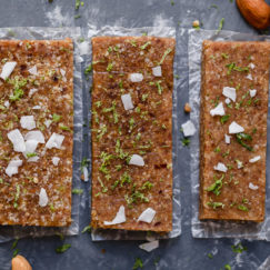 Three key lime energy bars lined up and topped with lime zest and coconut shreds