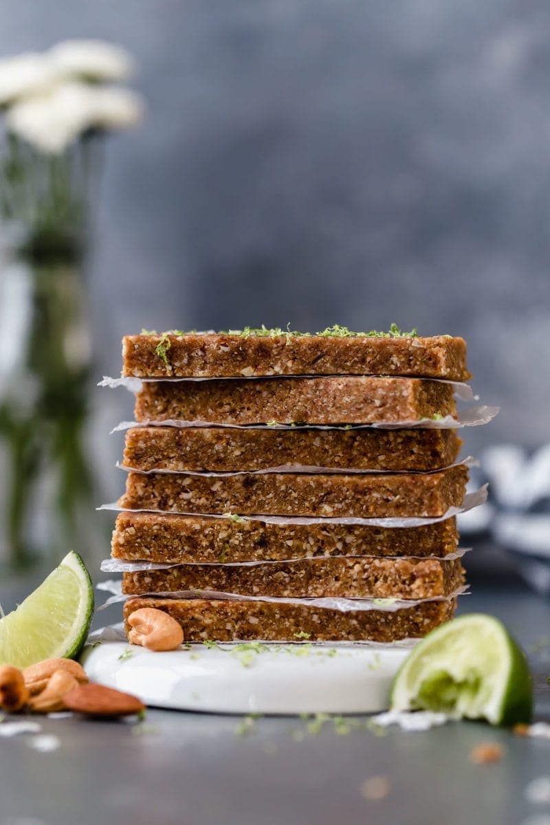 Seven Key Lime Energy Bars stacked on top of each other with parchment paper between each bar.