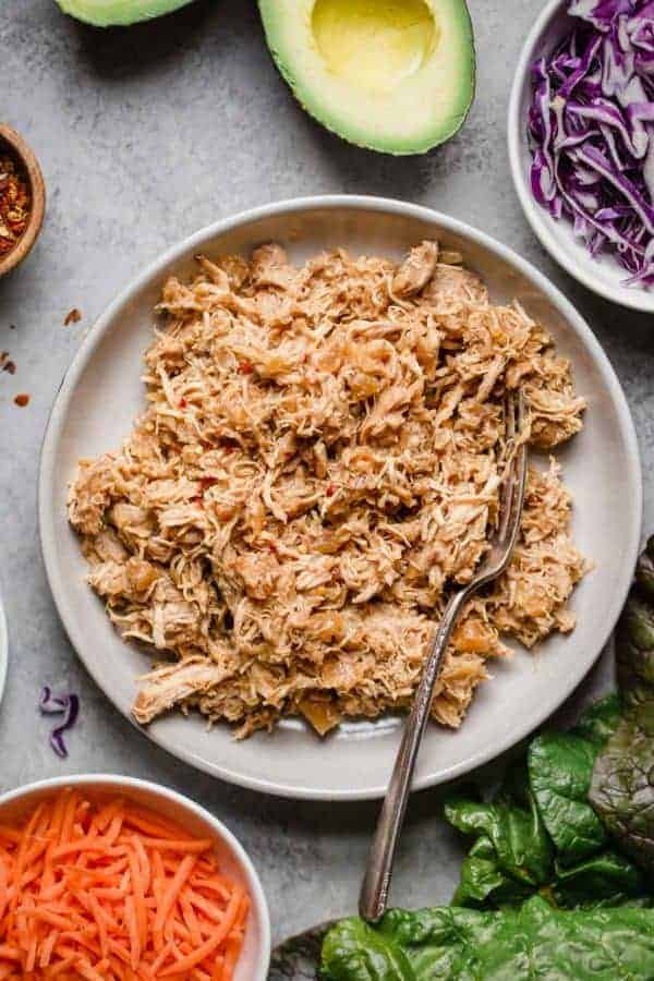 Slow Cooker Hawaiian Shredded Chicken cooked and shredded on a white plate