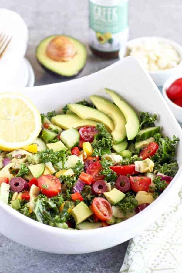 Greek Kale Salad with Avocado in a white bowl