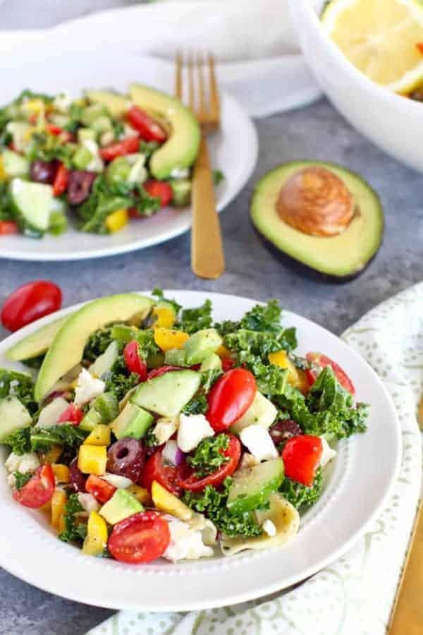 Greek Kale Salad with Avocado on a white plate
