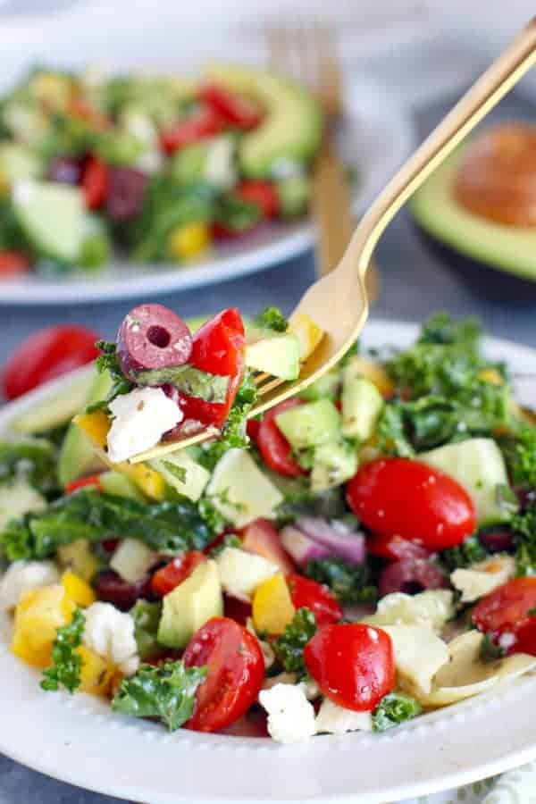 Greek Kale Salad with Avocado on a gold fork