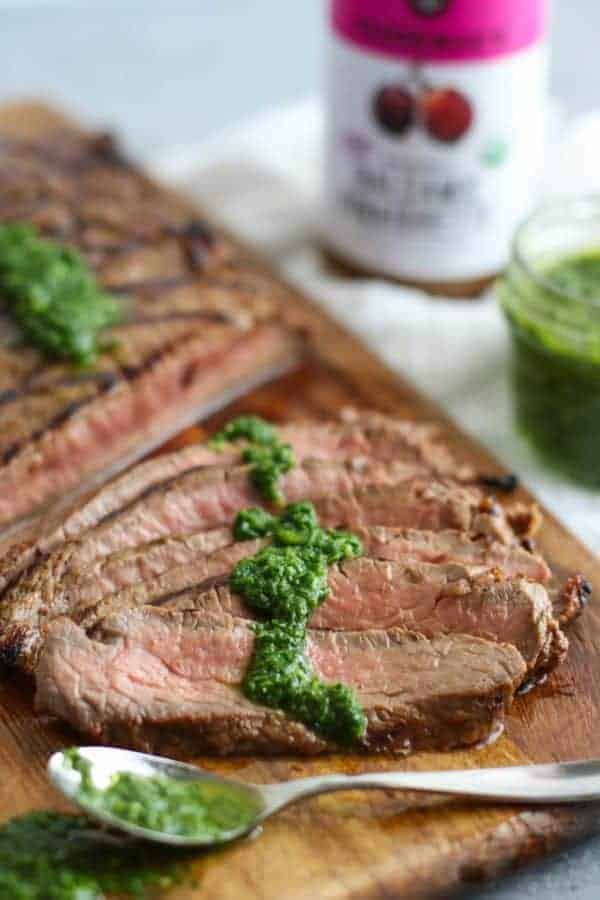 Balsamic Flank Steak with Chimichurri Sauce on wooden cutting board