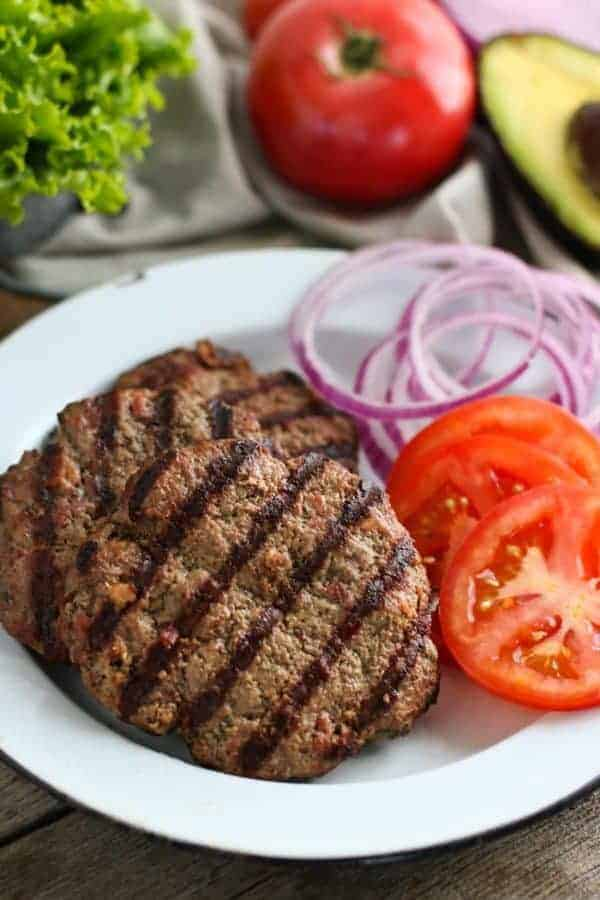 Grilled Bacon Burgers on a white plate with slice tomatoes and onion on the side