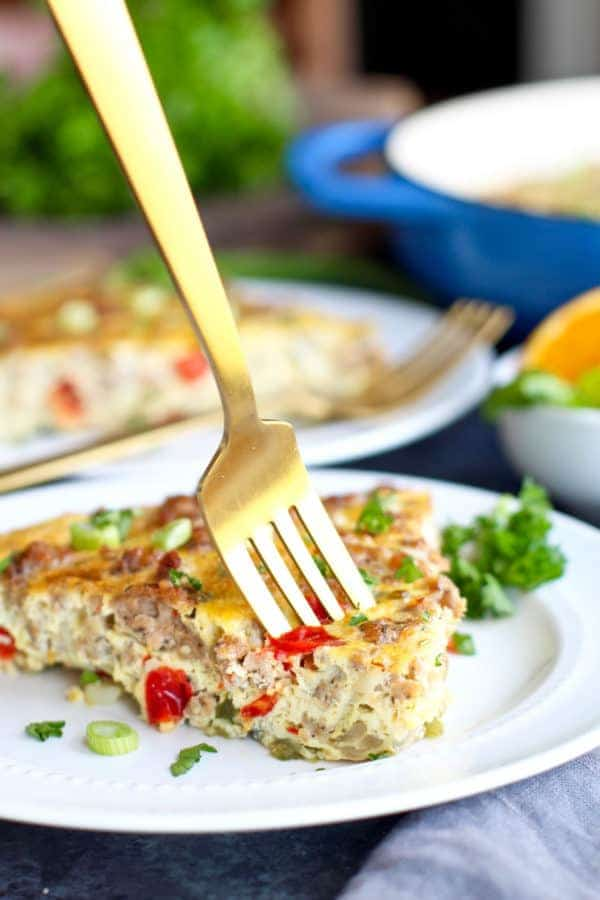 Sausage Hash Brown Egg Bake with a golden fork inserted in a piece on a white plate