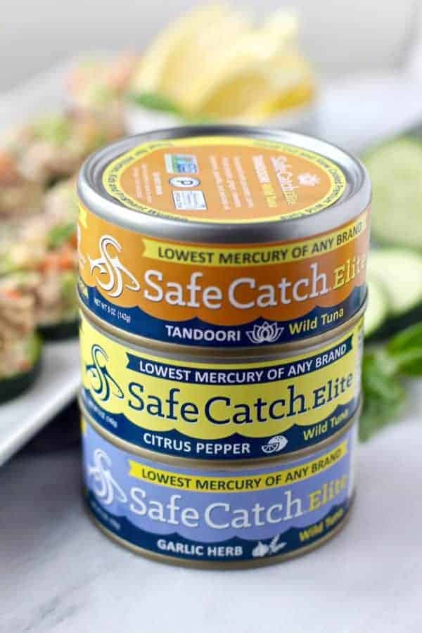 cans of SafeCatchElite Wild Tuna with a white plate of Cashew Tuna Salad Cucumber Bites in the background