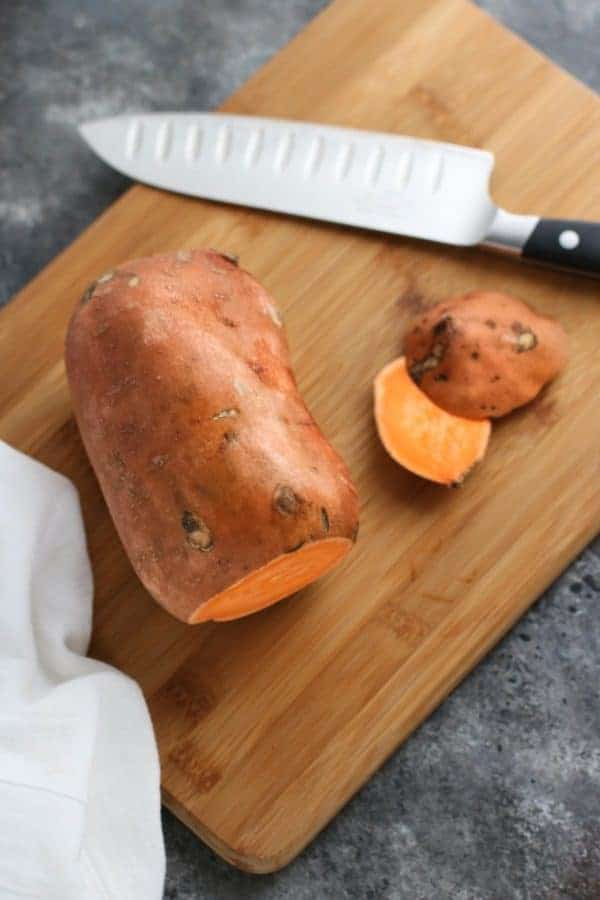 Oven Baked Sweet Potato Toast 4 Ways sweet potato on a wooden cutting board with a knife