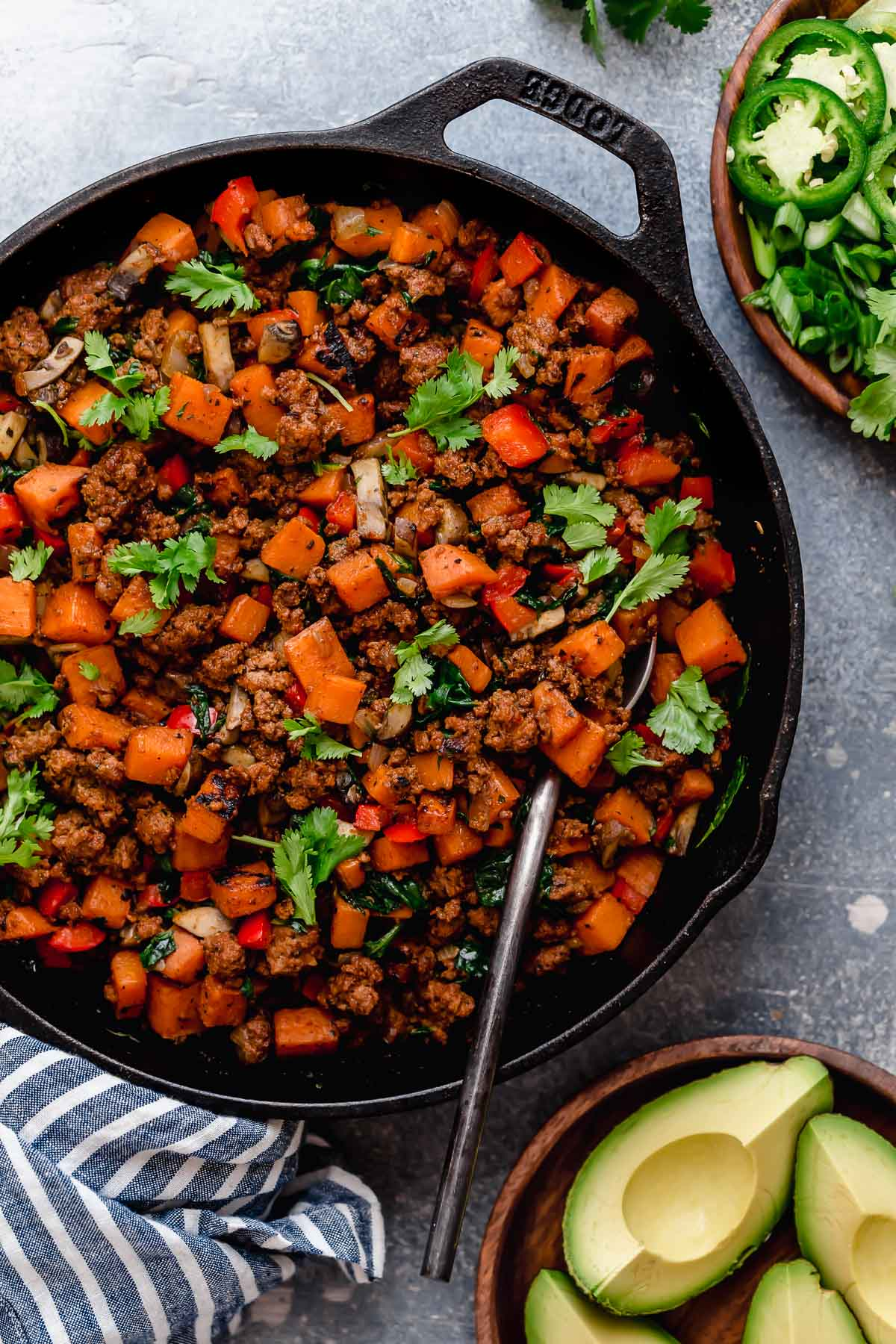 Tex-Mex Sweet Potato Hash in a black skillet with a spoon in it.